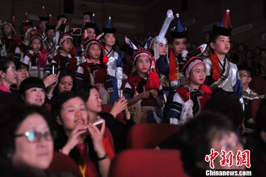 """图为合唱团小朋友挤在观众席观看""""团友""""演出。 任东 摄"""